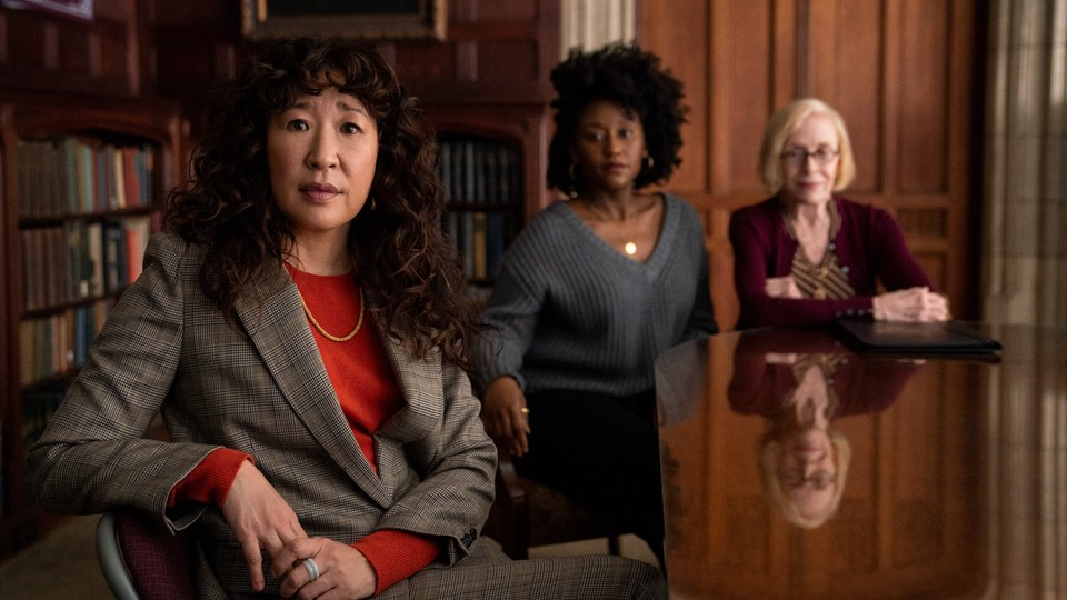 Sandra Oh sitting at a table in The Chair