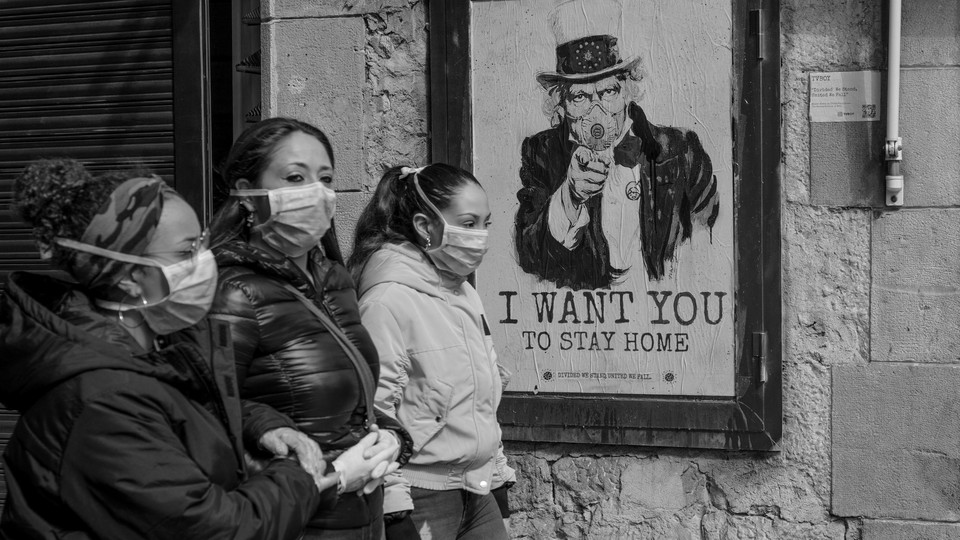 """Women wearing face masks passing by a sign a poster which says """"I want you to stay home."""""""