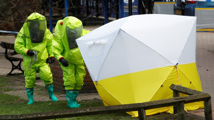 Two people in fluorescent suits approach a police tent