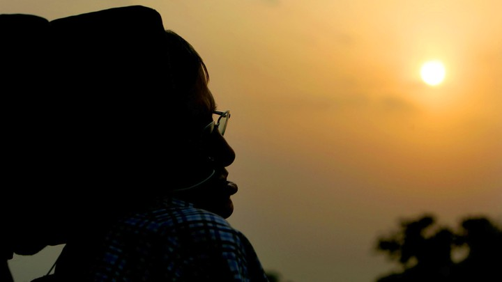 A silhouette of Stephen Hawking against a sunset