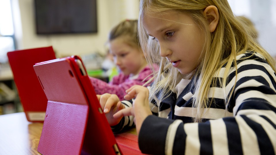 Two young girls sit at a desk with iPads.
