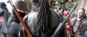 Walter Gibson wears two rifles strapped to his back