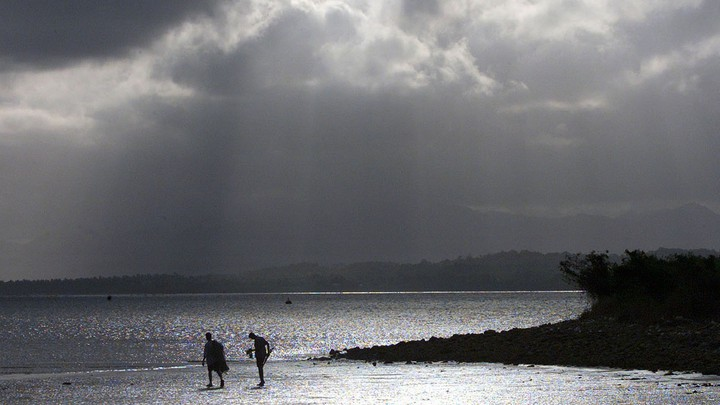 An afternoon storm looms above fishermen in Suva, Fiji