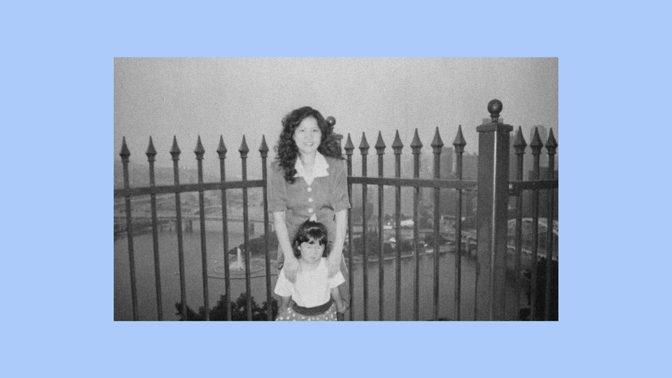 The author as a child with her mother near a gate, in black-and-white