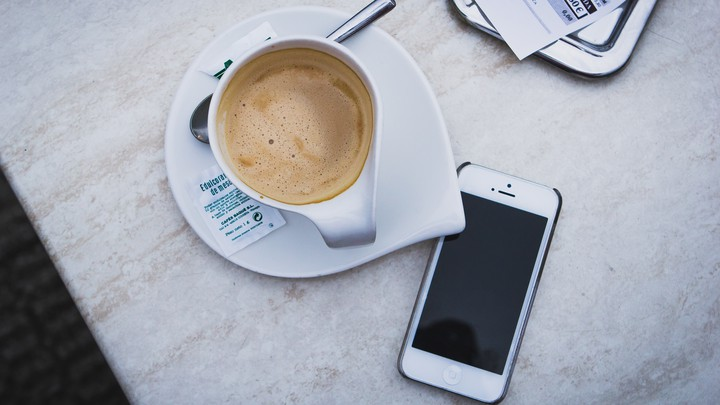 A smartphone sits unattended by a cup of coffee on a table.
