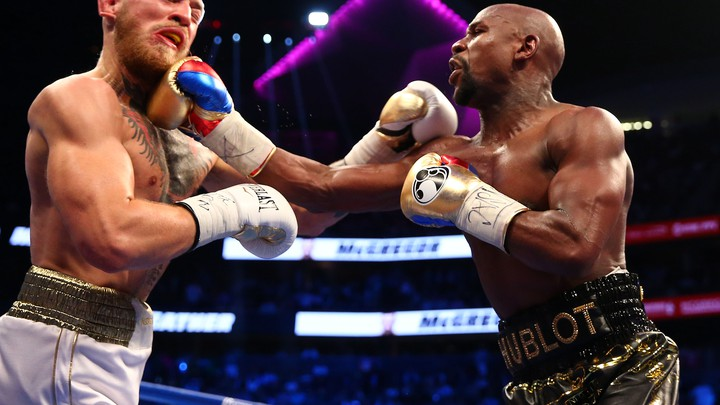 Floyd Mayweather Jr. lands a hit against Conor McGregor during a boxing match.