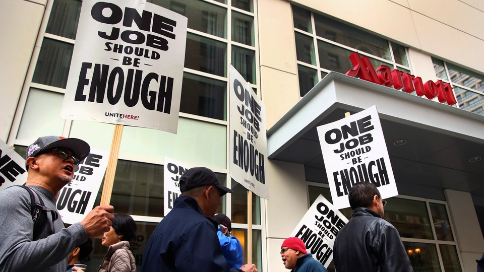 Hotel workers march and hold picket signs in front of a Marriott hotel.