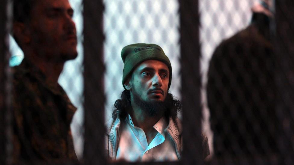 A suspected al-Qaeda militant stands behind bars.