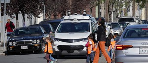 Children pass in front of a self-driving GM Bolt EV during a media event in San Francisco.