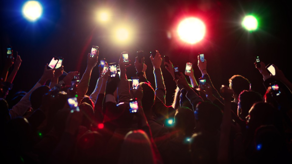 People in the crowd at an event hold their phones in the air