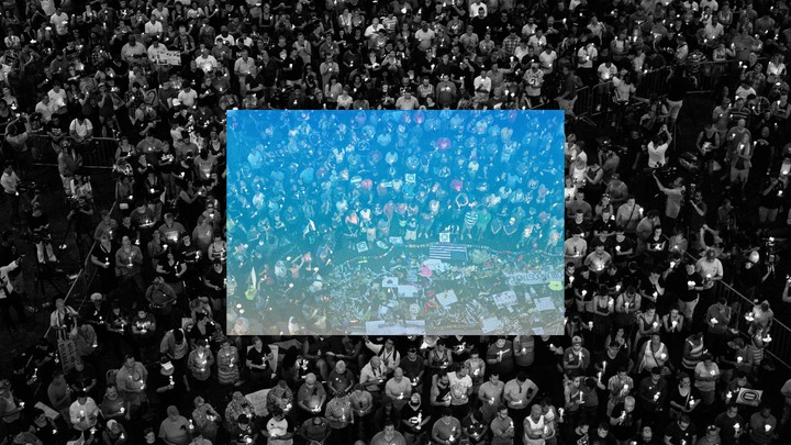 Black-and-white photo of a crowd of mourners with a square blue overlay in the middle
