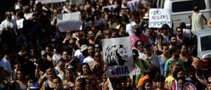 Protestors in Rio de Janeiro hold a picture of slain politician Marielle Franco, and a sign reading, 'Black lives are important' in Portuguese.