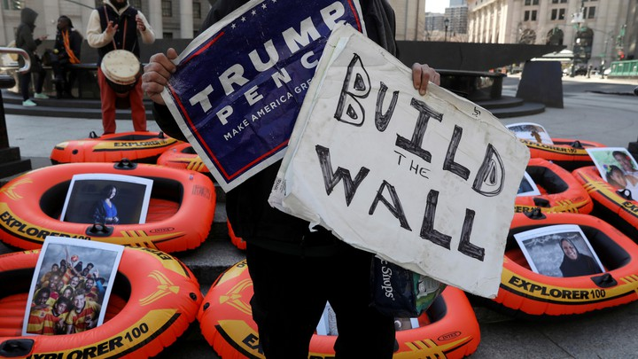 """A person holding a """"Trump, Pence"""" support sign and a poster reading """"Build the Wall"""" stands in front of rafts meant to display opposition to the U.S. refugee ban in New York City."""