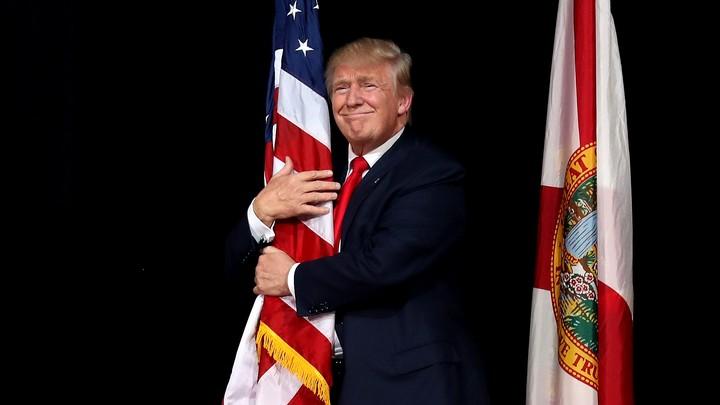 Donald Trump hugging an American flag