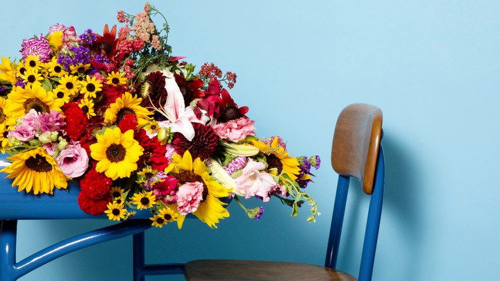 A profile view of a desk with flowers spilling off of it, against a blue background