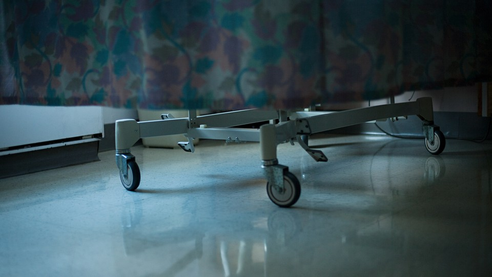 The bottom of a hospital bed is pictured being wheeled through a hospital.