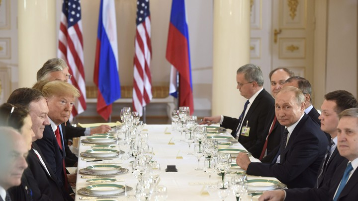 Trump and Putin are seated at a long table at a lunch meeting with other leaders and advisors.