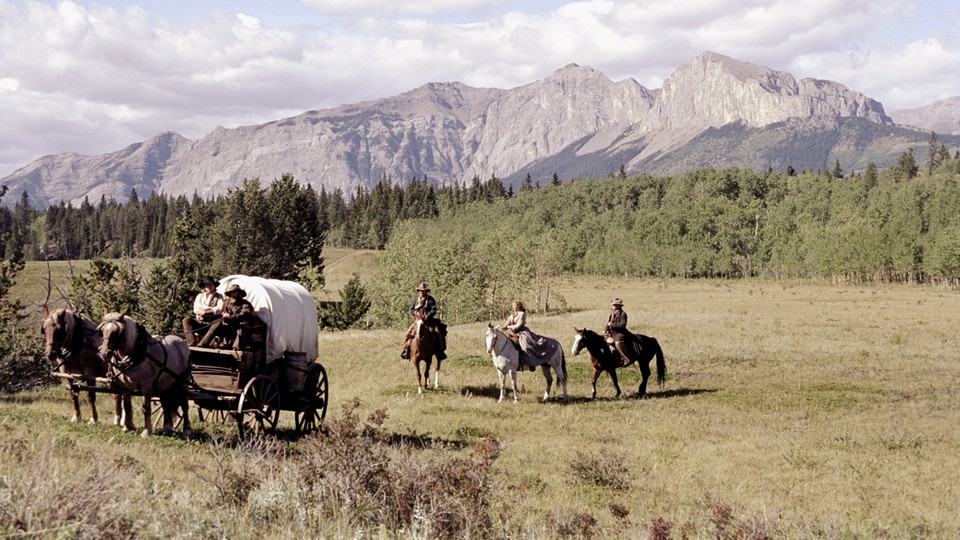 people ride in a covered wagon with mountains in the background