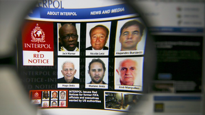 The homepage of the Interpol website is seen through a magnifying glass in this picture illustration taken in 2015.