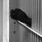 An inmates hands shown through bars holding a rosary