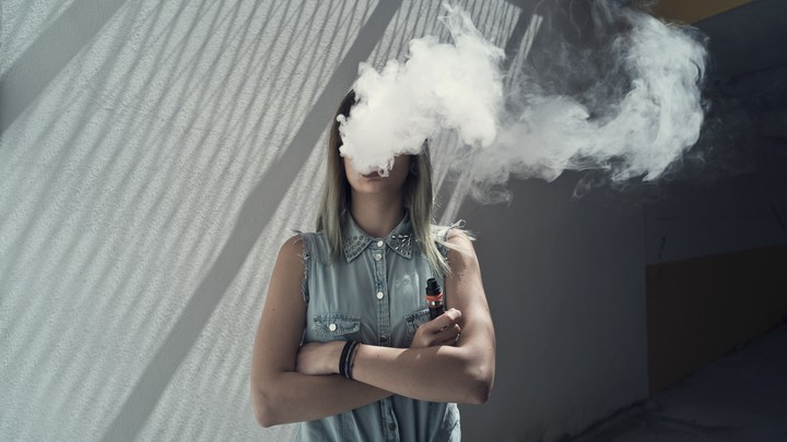 A woman's face is obscured by a cloud of vape smoke.