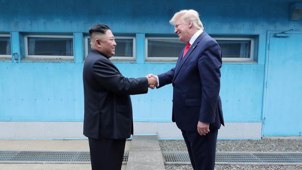 President Donald Trump shakes hands with Kim Jong Un.