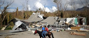 Local residents ride a horse by a house wiped out by Hurricane Maria in Jayuya, Puerto Rico.