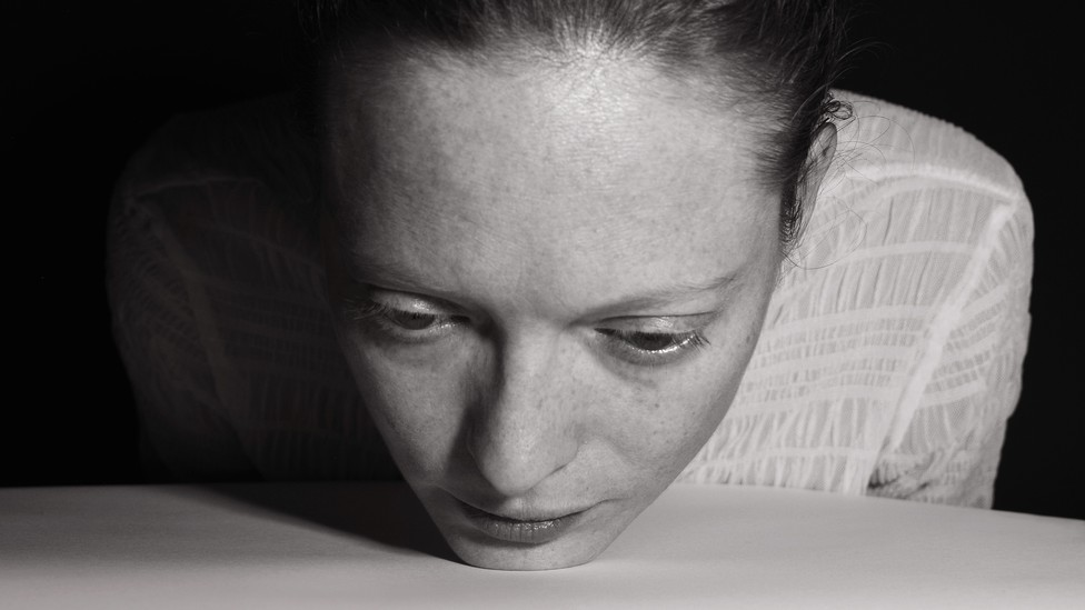 Black-and-white image of a woman placing her chin on the table