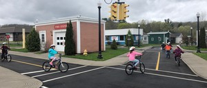 Children bike through a miniature town with scaled-down buildings and streets.