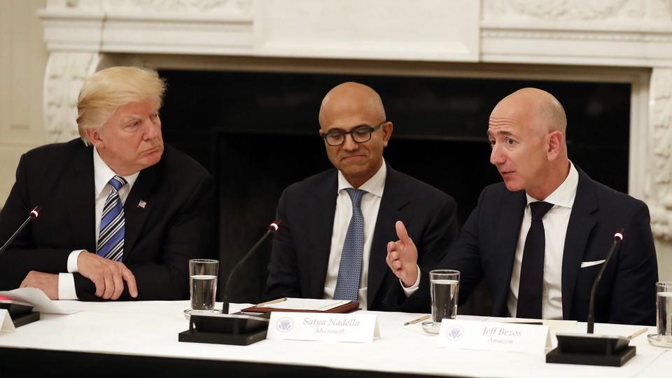Donald Trump, Satya Nadella, and Jeff Bezos seated at a table