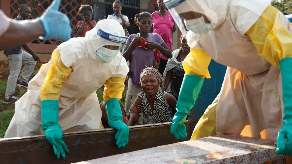 A mother of a child, suspected of dying from Ebola, cries near her child's coffin in Beni