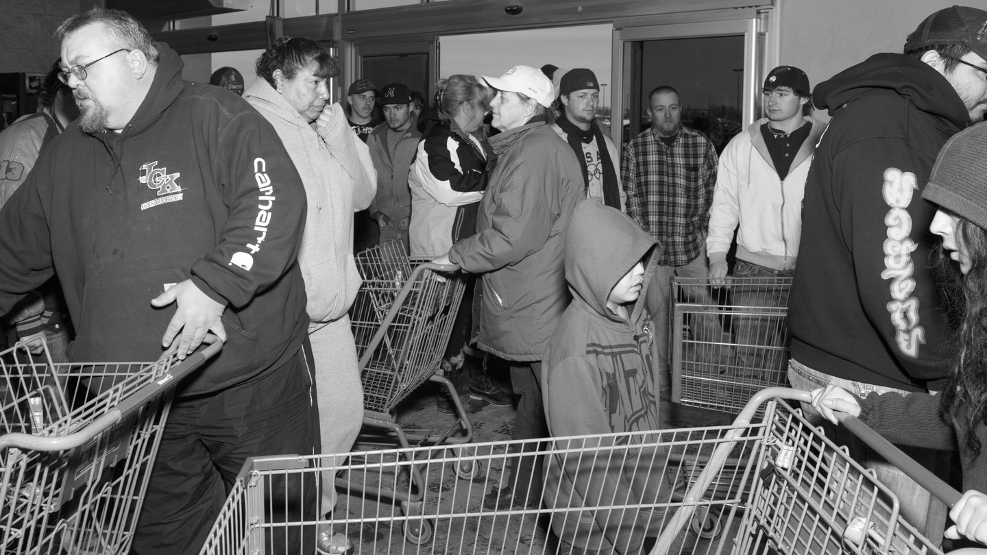 Customers push shopping carts while crowded in a small room.