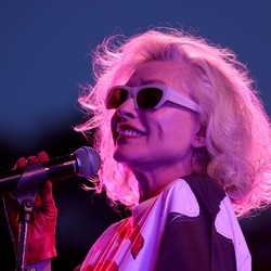 Performer Debbie Harry holds a microphone onstage.