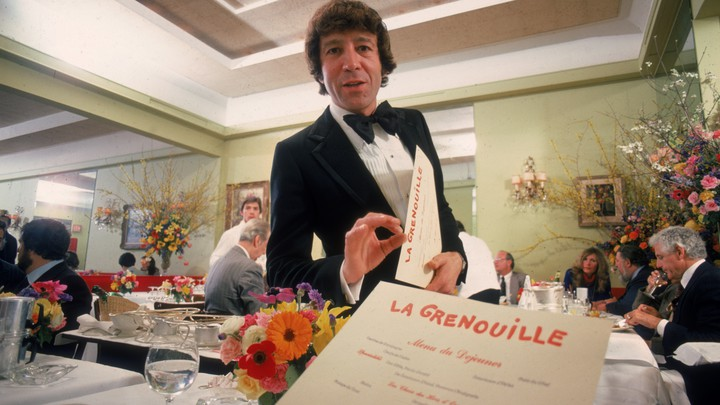 A diner's-eye view of a menu and waiter
