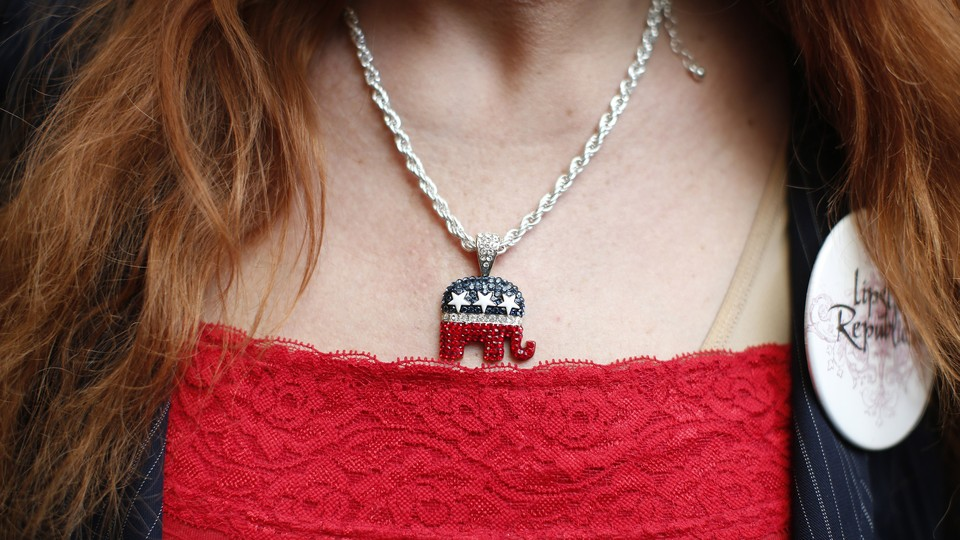 A close-up photograph of a woman wearing a red shirt and a sparkly necklace with a Republican elephant pendant