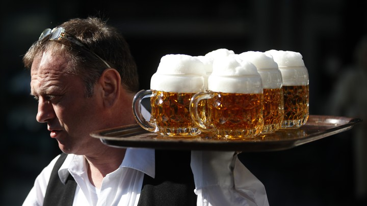 A waiter carries a tray of beers