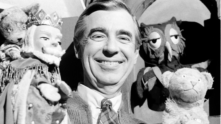 A photo of Fred Rogers holding a few puppets.