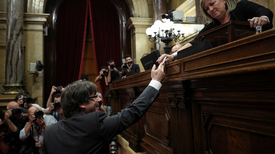 Catalan President Carles Puigdemont hands in his ballot during a vote on independence from Spain at the Catalan regional Parliament in Barcelona, Spain on October 27, 2017.