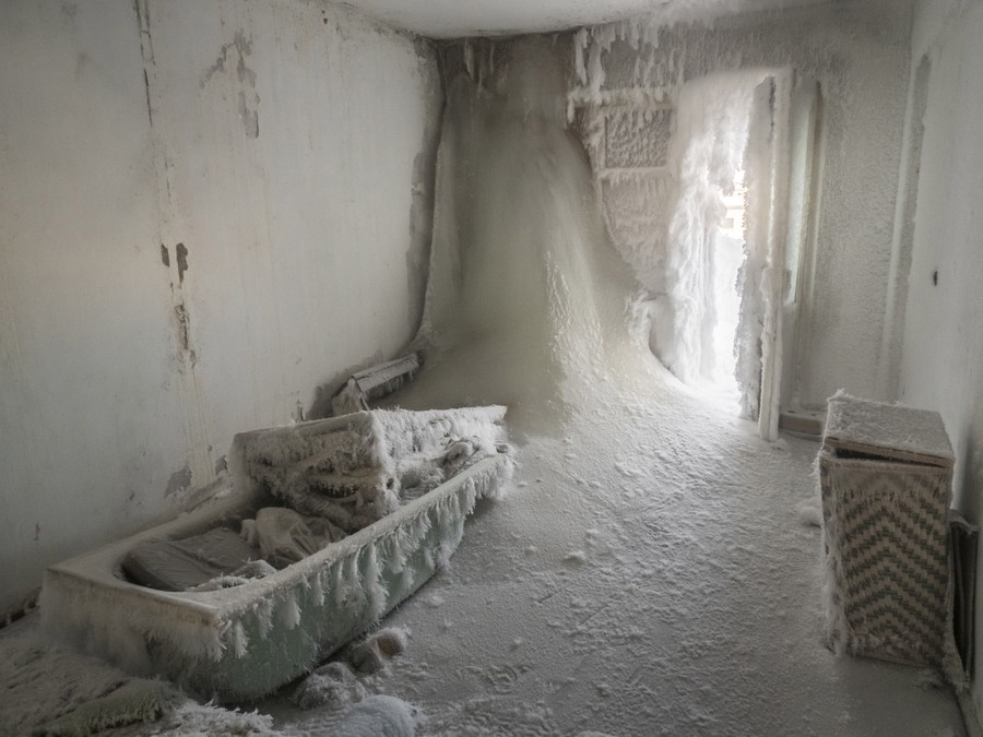 Huge volumes of ice intrude into a bathroom, entering from an open door, the walls and ceiling.