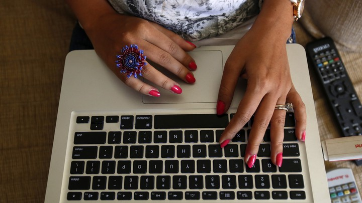A person types on an Apple laptop keyboard