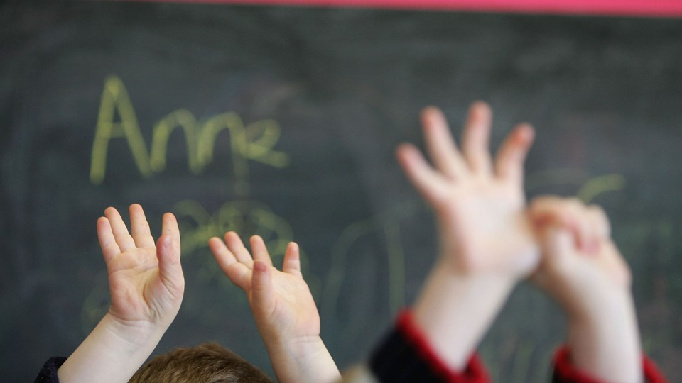 Children's hands in the air in front of a chalkboard