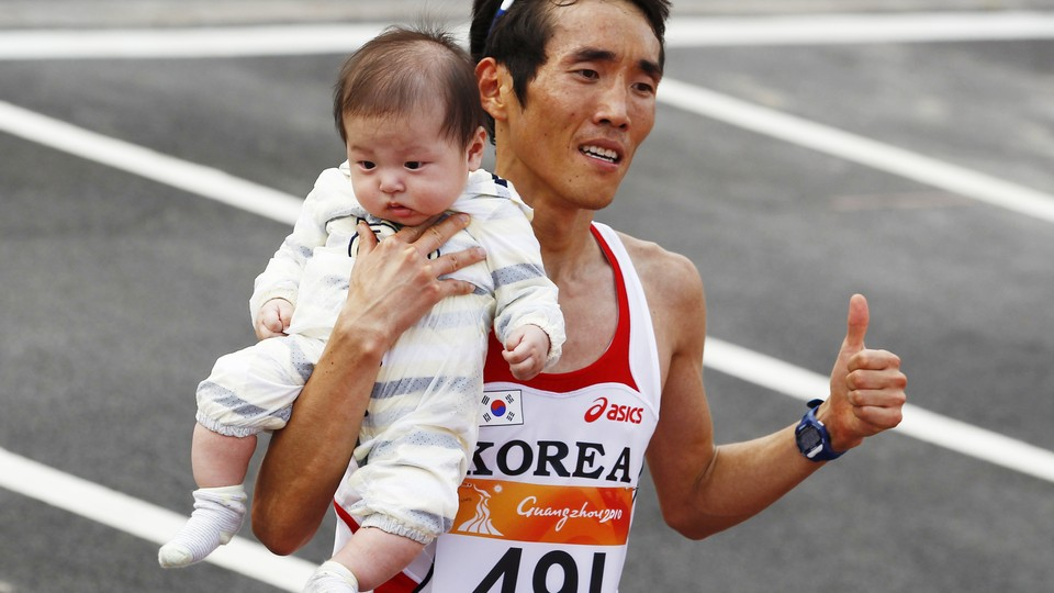 Ji Young-jun poses with his baby after winning the men's marathon at the 16th Asian Games.