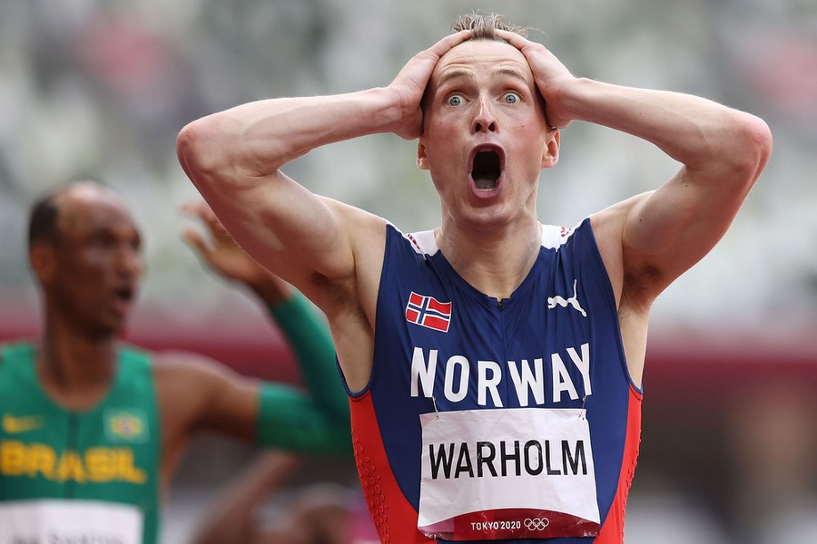 A runner reacts, hands to head, after setting a world record.