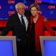 Bernie Sanders puts an arm around Elizabeth Warren.