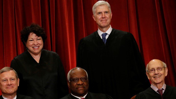 Supreme Court justices stand in front of a red backdrop.