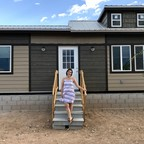 Elementary school teacher Sydney Scharer poses in front of her tiny home.