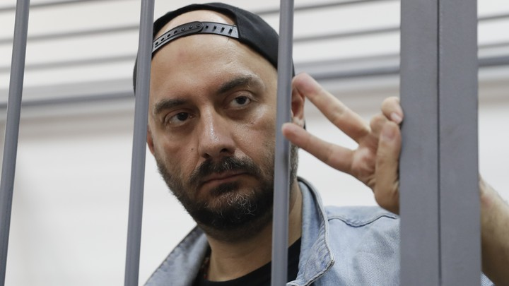 Serebrennikov makes a peace sign as he stands behind bars at a Moscow court hearing in September 2017.