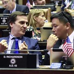 Two politicians talk while seated in a full assembly chamber.
