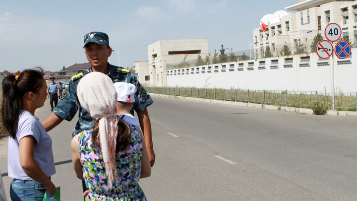 A member of Kyrgyz security forces addresses passers-by near the site of a bomb blast outside China's embassy in Bishkek, Kyrgyzstan.