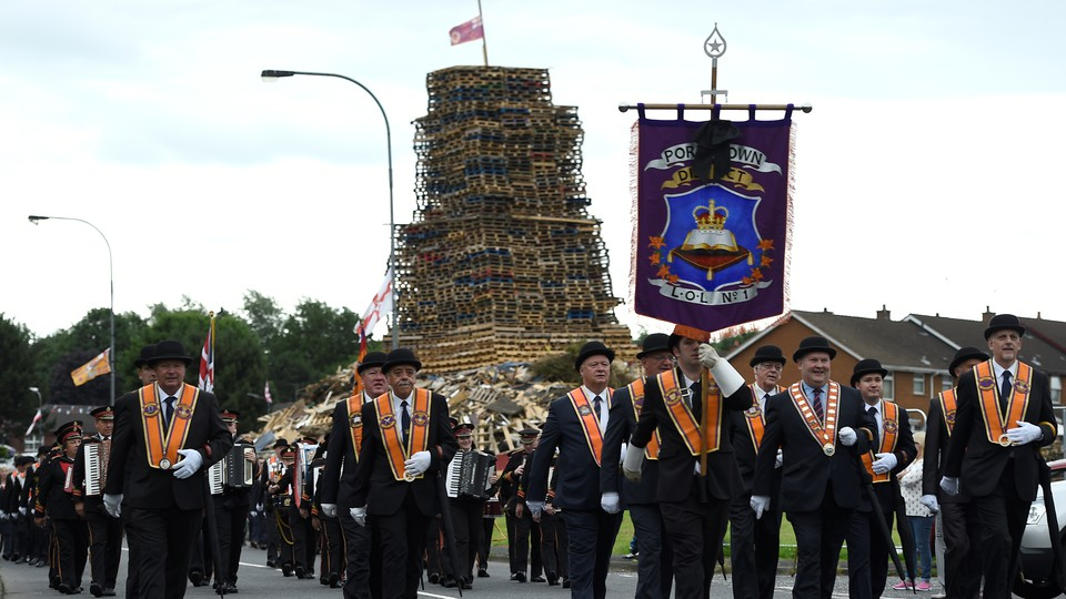 Participants in an Orange Order parade march past a bonfire pyre in Portadown, Northern Ireland.